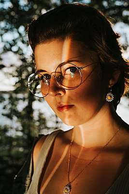 Girl with glasses in reflecting light - p1507m2196138 by Emma Grann
