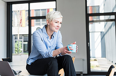Smiling woman with cup of coffee sitting on table in office - p300m1581360 von Uwe Umstätter