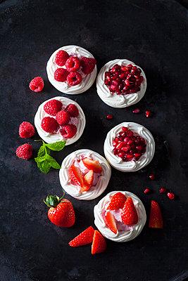 Meringue pastries garnished with whipped cream, berries and pomegranate seed - p300m1588048 von Dieter Heinemann