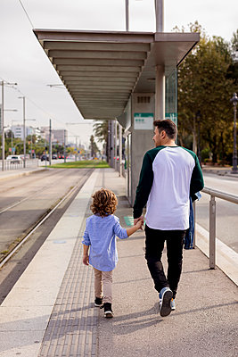 Rear view of father and son walking hand in hand at tram stop in the city - p300m2070424 von Mauro Grigollo