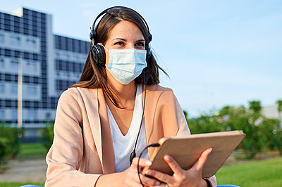 Woman looking away wearing protective face mask using digital tablet sitting in public park - p300m2226818 by Kiko Jimenez