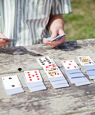 Man playing cards - p956m1044293 by Anna Quinn