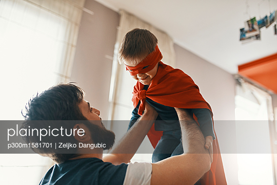 Father playing with his little son dressed up as a superhero - p300m1581701 von Zeljko Dangubic
