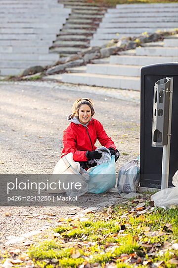 Portrait of female volunteer crouching with plastic waste by garbage can - p426m2213258 by Maskot