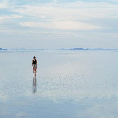 A woman standing on the flooded Bonneville Salt Flats, at dusk. - p1100m875902f by Paul Edmondson