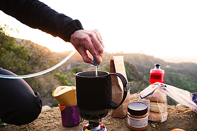 camper making coffee in mountains at sunrise - p1166m2157082 by Cavan Images