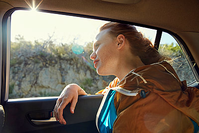 Young woman in a car looking out of window - p300m1460712 by Martina Ferrari