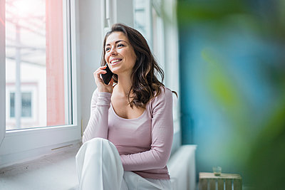 Portrait of young woman on the phone looking out of window - p300m1535649 by Robijn Page
