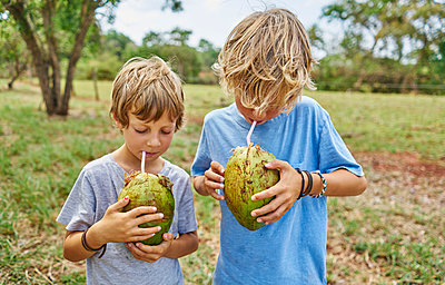 Brazil, Bonito, two boys drinking from coconut with straws - p300m2059586 by Stefan Schütz