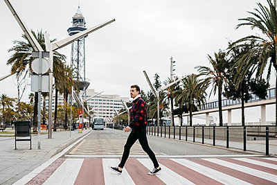 Young man with casual clothes walking on pedestrian crossing in Barcelona - p300m2080831 by Josep Rovirosa