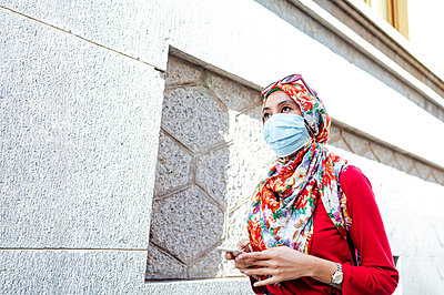 Woman in hijab wearing protective face mask holding smart phone while walking by wall during COVID-19 - p300m2240712 by Jose Luis CARRASCOSA