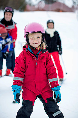 Portrait of girl in ski-wear with family in background - p426m803142f by Maskot