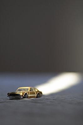 Potsdam, ein goldenes Spielzeugauto steht im Sonnenlicht - p627m1035262 von Hendrik Rauch