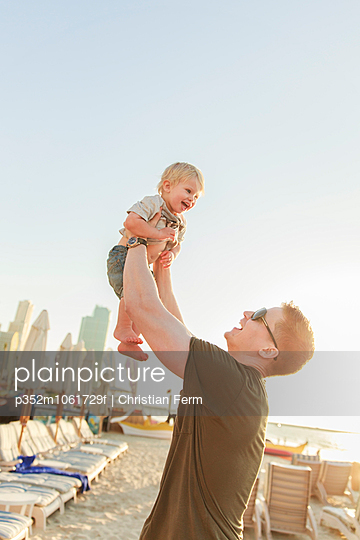 United Arab Emirates, Dubai, Man holding son (12-17 months) on beach