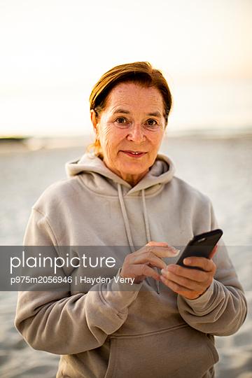 Frau benutzt ein Smartphone - p975m2056946 von Hayden Verry