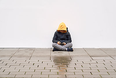 Boy using his mobile in the street with a white wall background - p1166m2136934 by Cavan Images