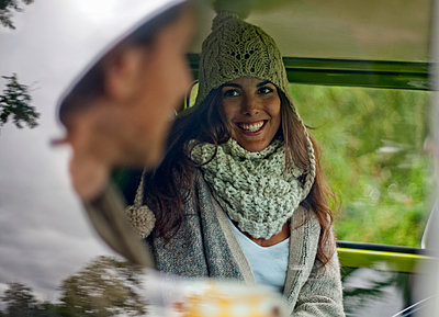 Beautiful woman smiling while talking with boyfriend in campervan - p300m2250214 by LOUIS CHRISTIAN