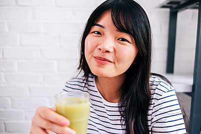 Young woman holding healthy smoothie at home - p300m2293301 by Angel Santana Garcia