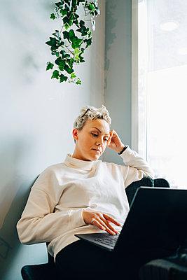 Female entrepreneur using laptop in office - p426m2259495 by Maskot