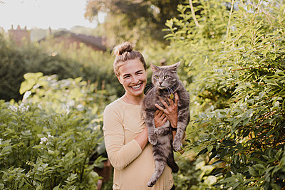 Woman gardener carrying cat in garden - p429m2145955 by Sara Monika