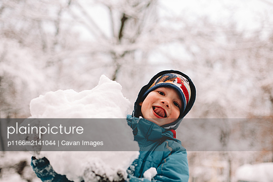 Happy boy sticking out tongue while playing with snow in winter - p1166m2141044 by Cavan Images