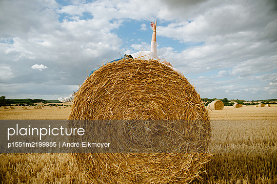 Woman lying on bale of straw - p1551m2199985 by André Eikmeyer
