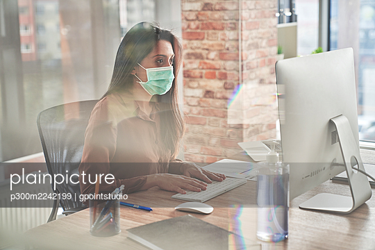 Mid adult woman working on computer on desk seen through glass during pandemic - p300m2242199 by gpointstudio