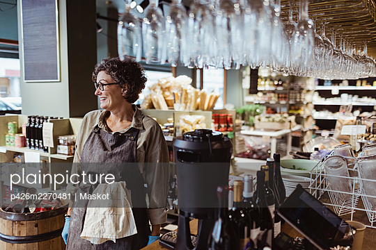Happy female owner looking away while standing in deli store - p426m2270481 by Maskot