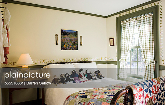 Small colonial bedroom with collection of amish dolls on bed