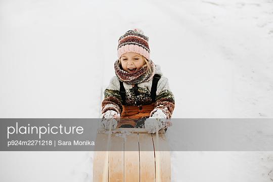 Canada, Ontario, Smiling girl (2-3) on toboggan - p924m2271218 by Sara Monika
