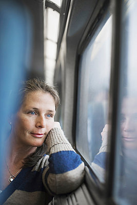 A woman sitting at a window seat in a train carriage, resting her head on her hand. Looking into the distance.  - p1100m876836f by Tim Pannell