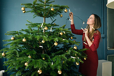Woman decorating Christmas tree - p300m2005457 by Robijn Page
