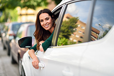 Smiling young woman leaning out the window of her car in the city - p300m2012657 by Javier Sánchez Mingorance