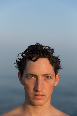 Young man with wet hair - p552m1564898 by Leander Hopf