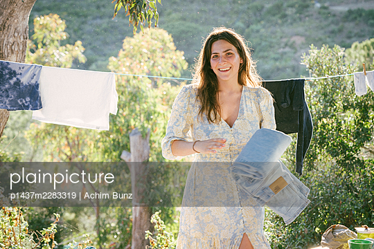 Young woman hangs out the washing - p1437m2283319 by Achim Bunz
