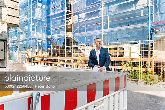 Male engineer looking away while standing by barricade at construction site - p300m2256438 by Peter Scholl