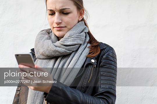 Frustrated young woman using her smartphone - p300m2277267 by Jean Schwarz