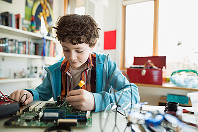 Boy assembling circuit board in bedroom - p1192m1129529f by Hero Images