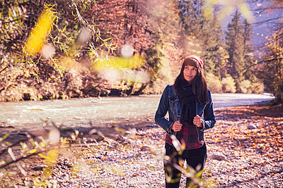 Woman wearing red woolly hat and denim jacket at riverside - p300m2160099 by Studio 27