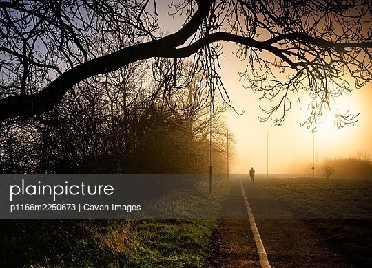 Woman silhouette walking jogging in a foggy morning sunrise in England - p1166m2250673 by Cavan Images
