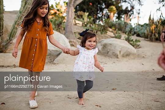 Sisters Holding Hands & Walking Through Desert Garden in San Diego - p1166m2292775 by Cavan Images