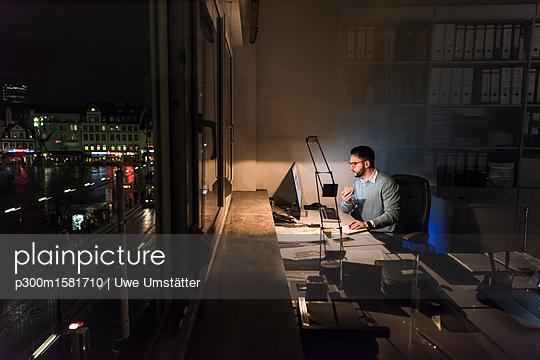 Businessman working on computer in office at night - p300m1581710 von Uwe Umstätter