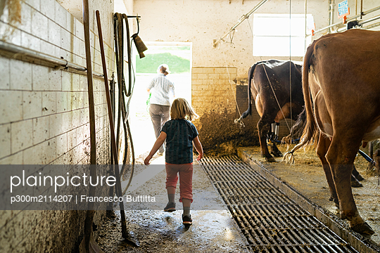 Daughter with mother leaving cow stable - p300m2114207 von Francesco Buttitta