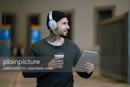 Smiling hipster man with coffee cup holding digital tablet while looking away - p300m2252113 by Jose Carlos Ichiro