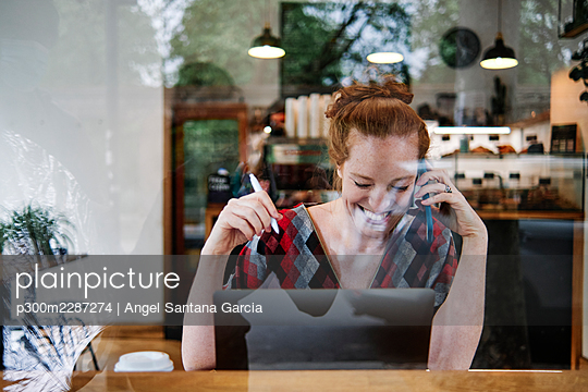 Happy woman talking on mobile phone while sitting at coffee shop - p300m2287274 by Angel Santana Garcia
