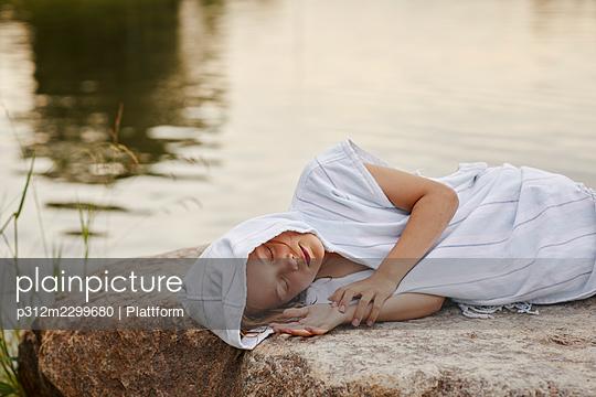 Girl napping at lakeside - p312m2299680 by Plattform