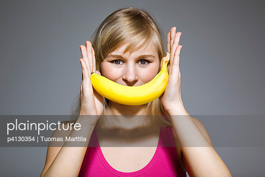 Young woman with banana - p4130354 by Tuomas Marttila