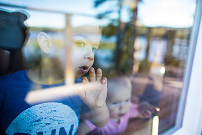 Brother and sister look out window in anticipation and wonder. - p1166m2153367 by Cavan Images