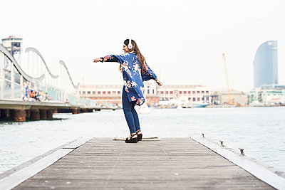 Spain, Barcelona, happy young woman with headphones dancing on jetty - p300m2012624 by Juan Novakosky