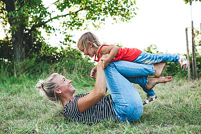Happy mother playing with daughter on meadow - p300m2058842 by Epiximages